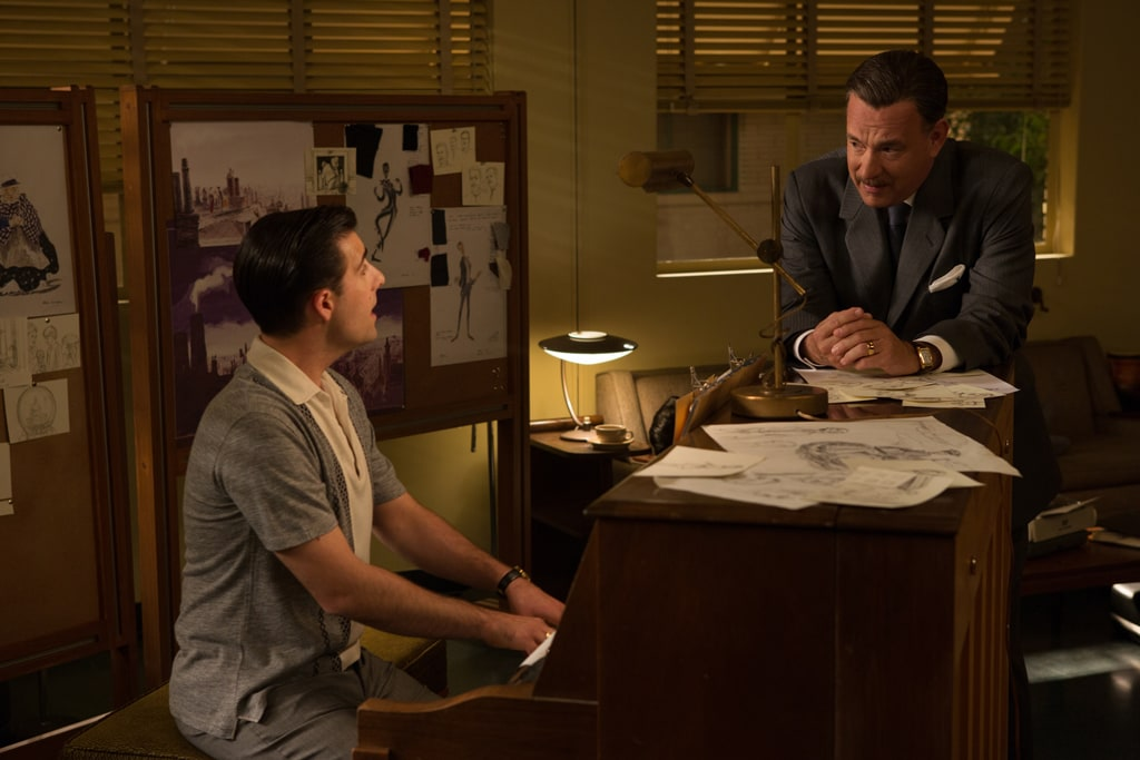 """Actor Jason Schwartzman (as Richard Sherman) playing a piano and actor Tom Hanks (as Walt Disney) leaning against the piano in the movie """"Saving Mr. Banks""""."""