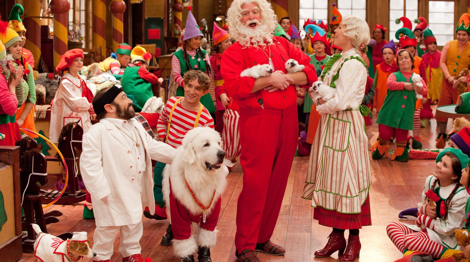 Santa, Mrs. Clause, and his dog standing with elves in Santa's workshop