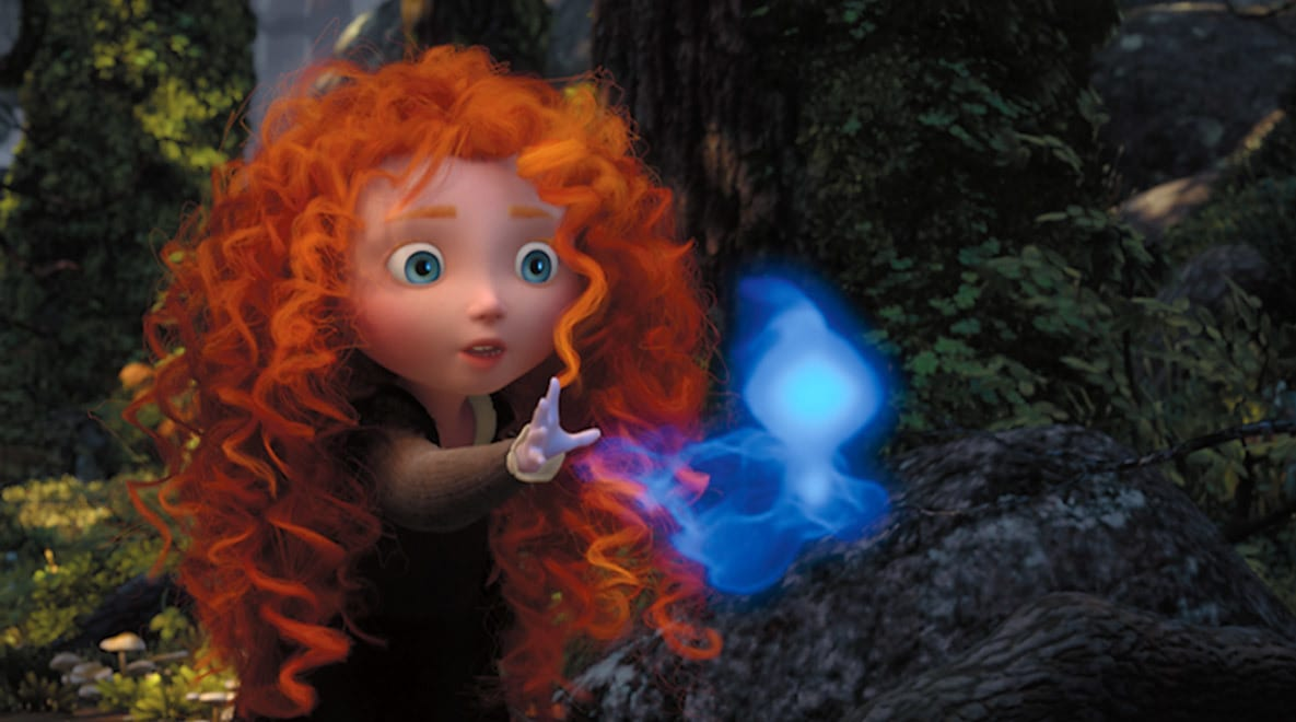 A young Merida, voiced by Peigi Barker, reaching for a blue Wisp in the movie Brave