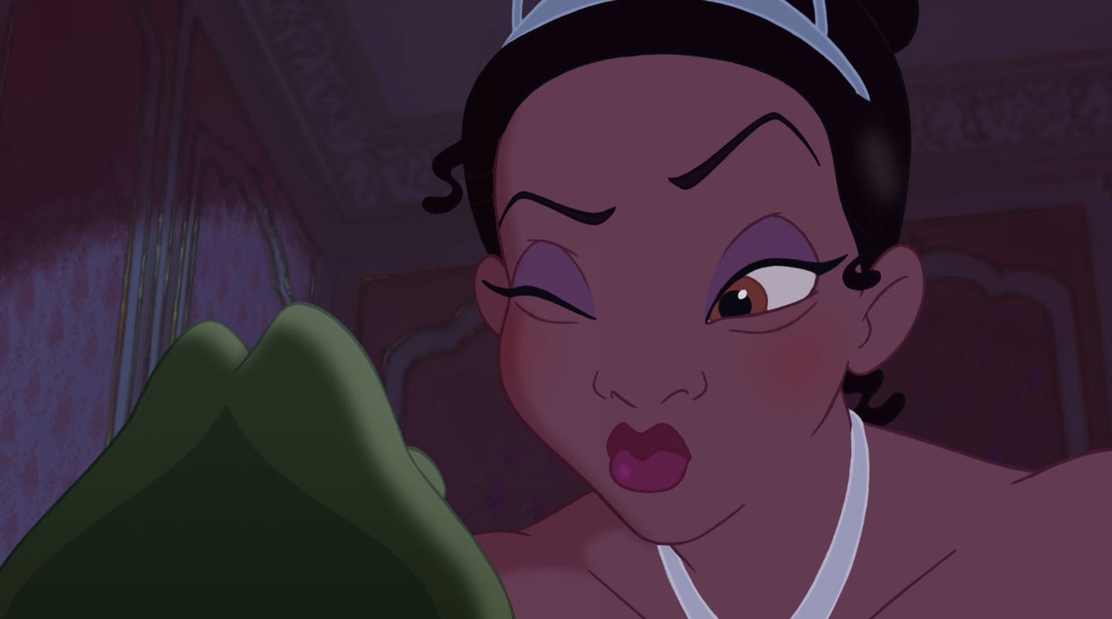 Tiana puckers her lips to kiss the frog version of Prince Nave
