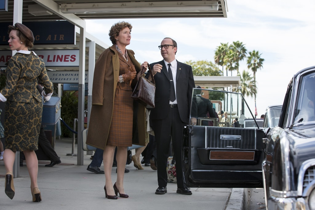 """Actors Emma Thompson (as P.L. Travers) and Paul Giamatti (as Ralph) on a sidewalk about to enter a car in the movie """"Saving Mr. Banks""""."""