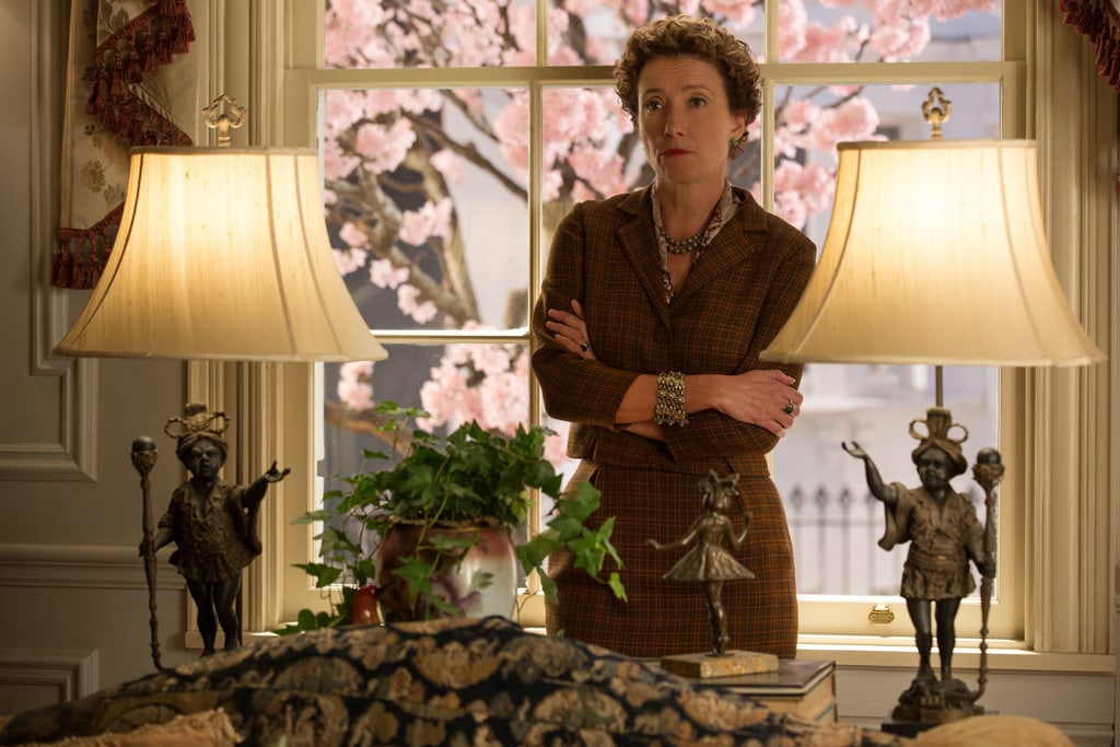 """Actor Emma Thompson as P.L. Travers standing behind a couch between two lights in the movie """"Saving Mr. Banks""""."""