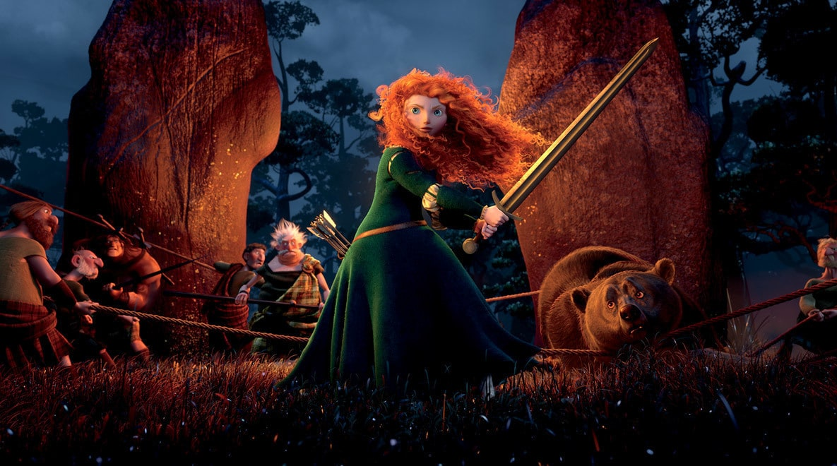 Merida, voiced by Kelly Macdonald, wielding a sword with other highlanders in the the background in the movie Brave