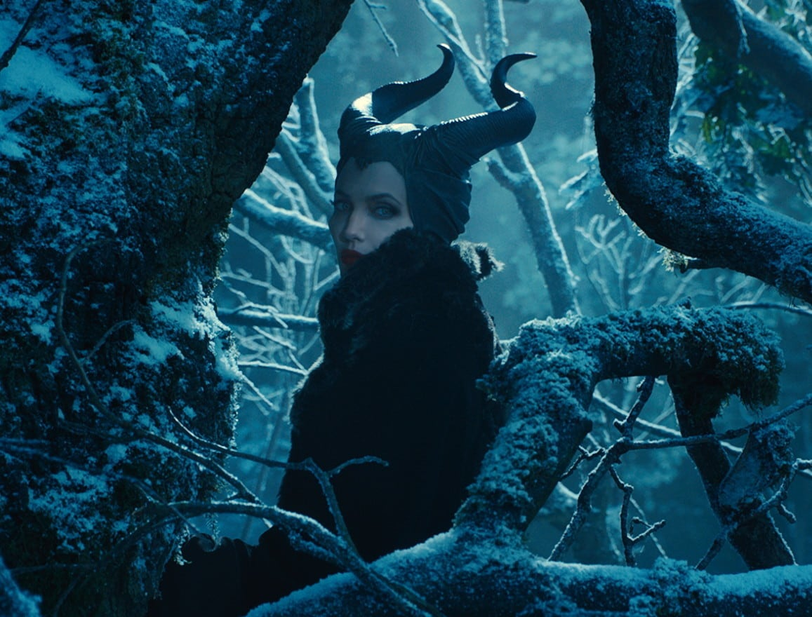 """Angelina Jolie as Maleficent surrounded by tree branches in the dark in the movie """"Maleficent"""""""