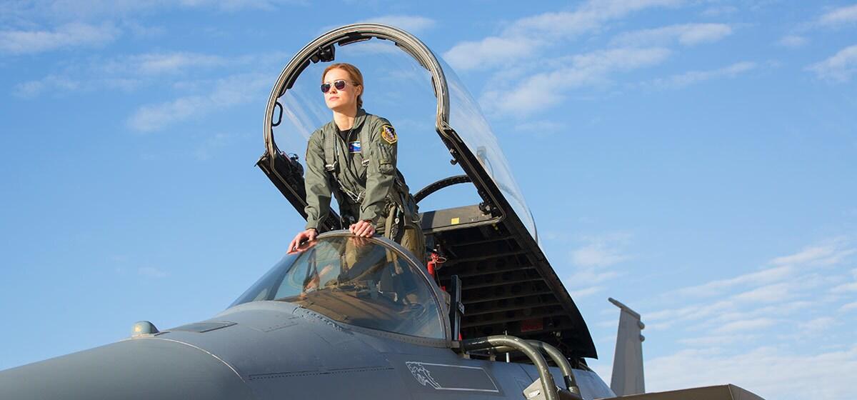 Brie Larson (Carol Danvers) standing on the seat of a fighter jet in Marvel Studios' Captain Marvel