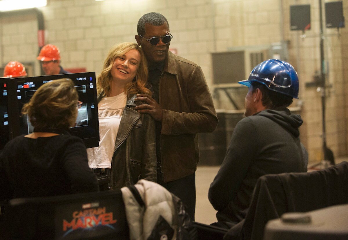 Brie Larson and Samuel L. Jackson on the set of Captain Marvel in front of screen, director and crew member in blue hard hat