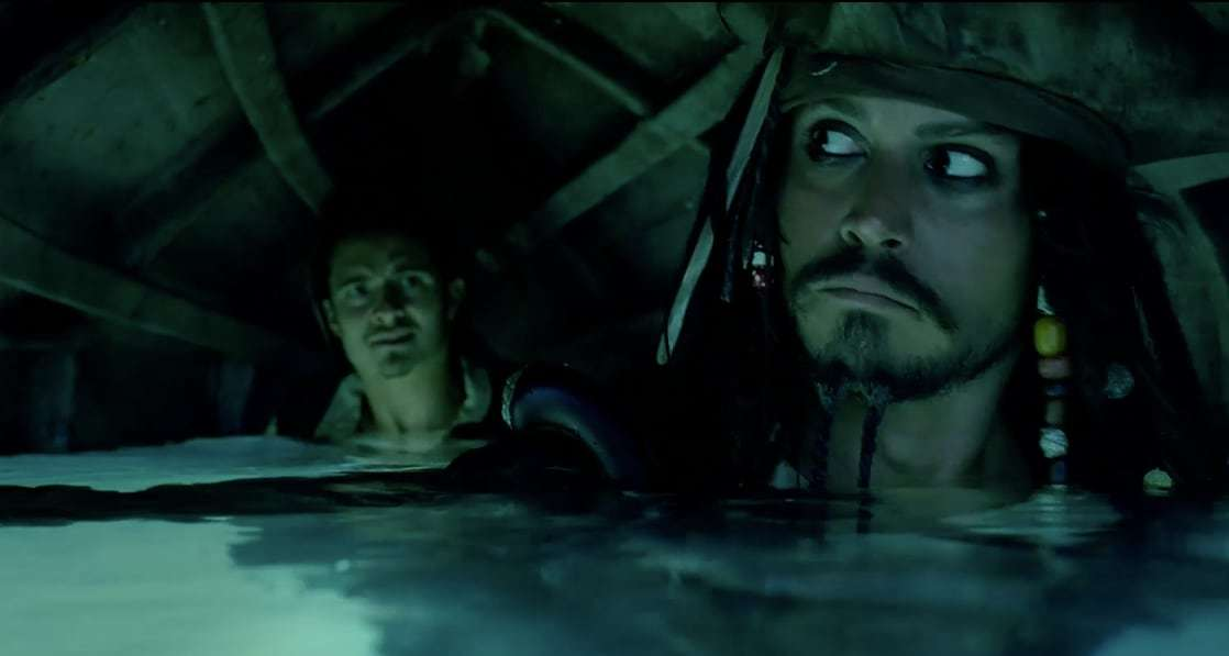 Actors Johnny Depp (Captain Jack) and Orlando Bloom (Will Turner) under a boat.