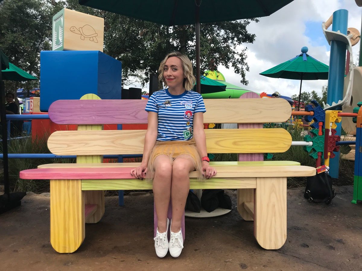 Oh My Disney Host Michelle Lema sitting on the Popsicle Stick Bench at Toy Story Land in Walt Disney World