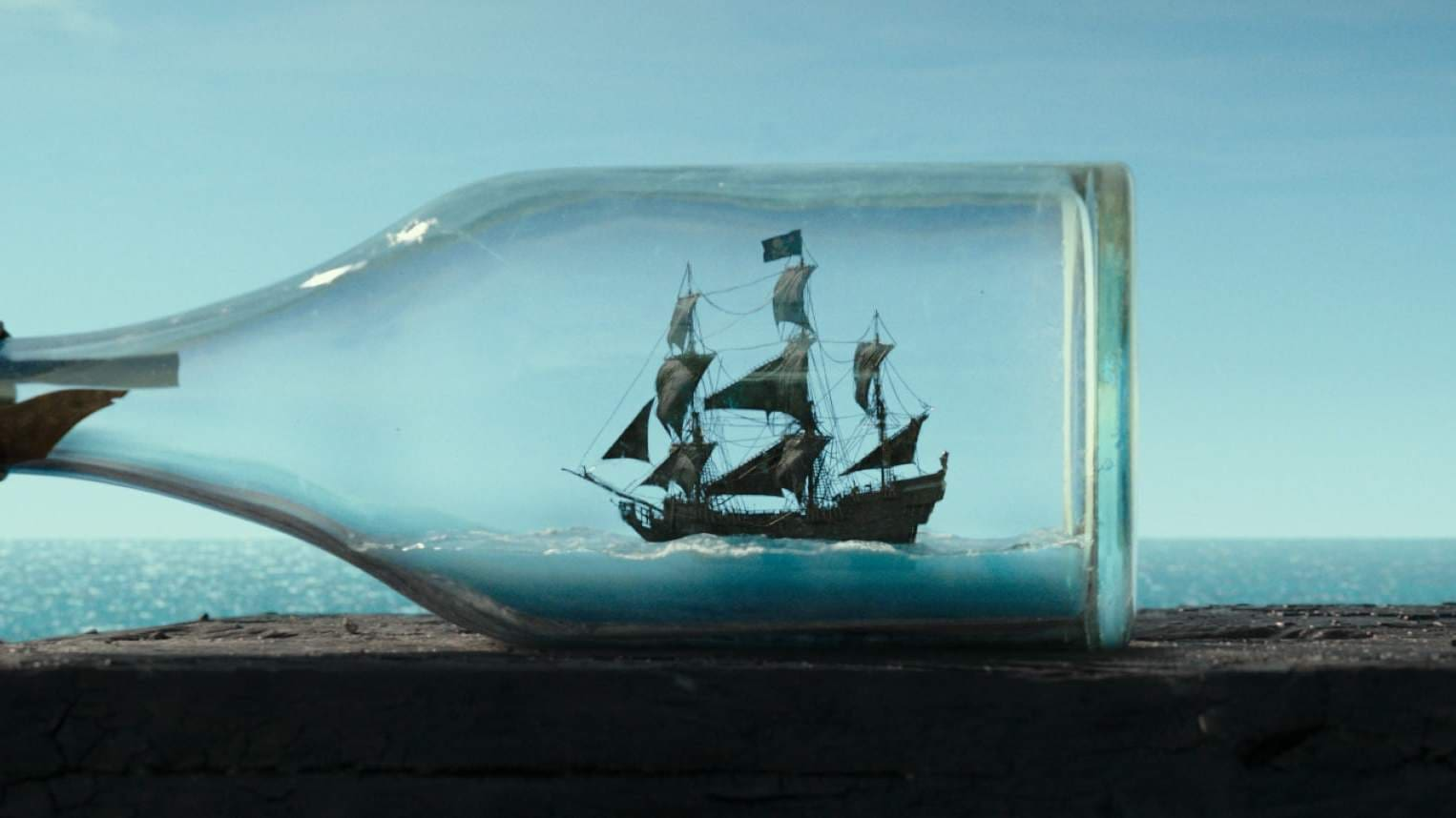 Image of a ship passing behind a glass bottle giving the illusion of a ship in a bottle in the movie Pirates of the Caribbean: Dead Men Tell No Tales