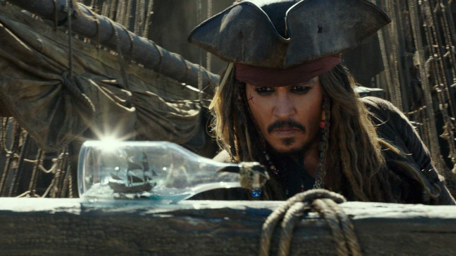 Captain Jack Sparrow, played by Johnny Depp, looking at a ship in a bottle in the movie Pirates of the Caribbean: Dead Men Tell No Tales