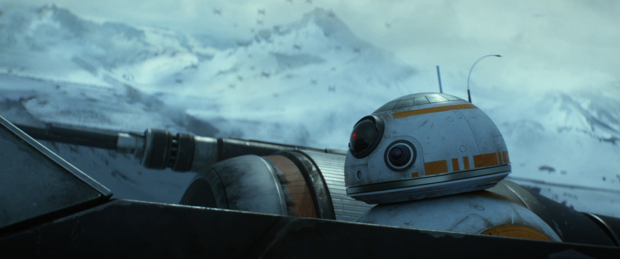 BB-8 an astro mech in the back of an X-wing, as TIE fighters close in.