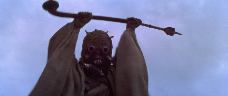 A Tusken Raider aggressively raising it's rifle