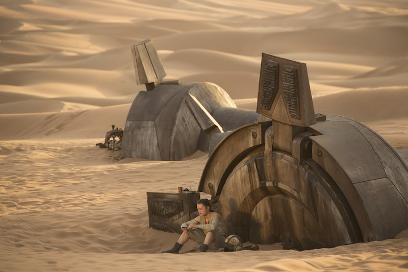 Rey sitting amongst the remains of a derelict AT-AT