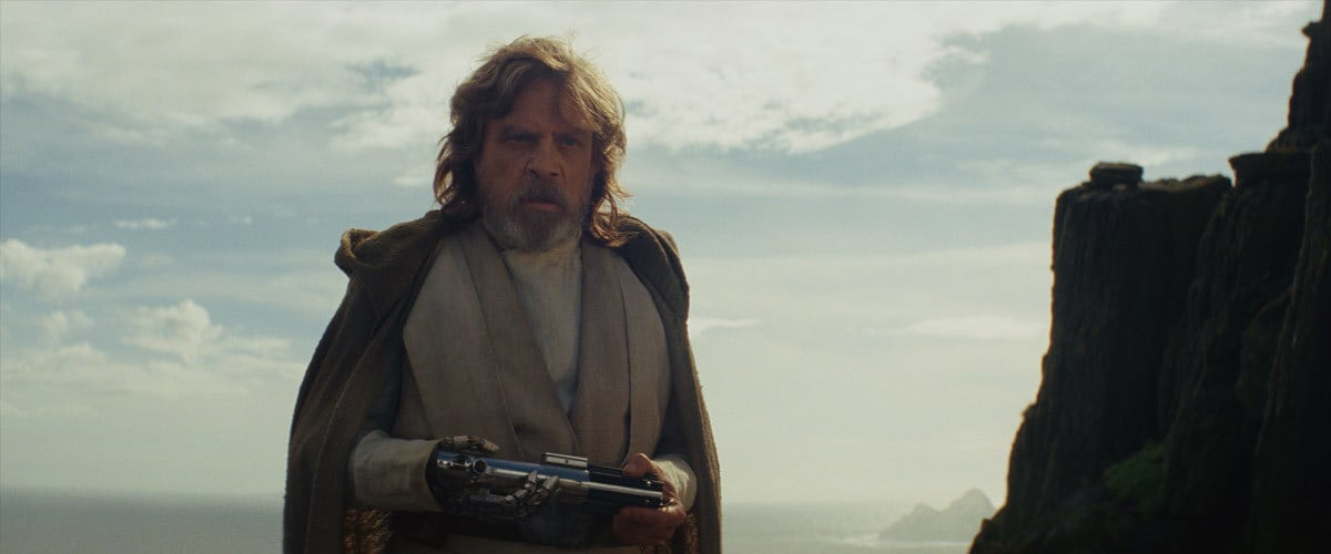 An aged Luke Skywalker holding his father's lightsaber on Ahch-To