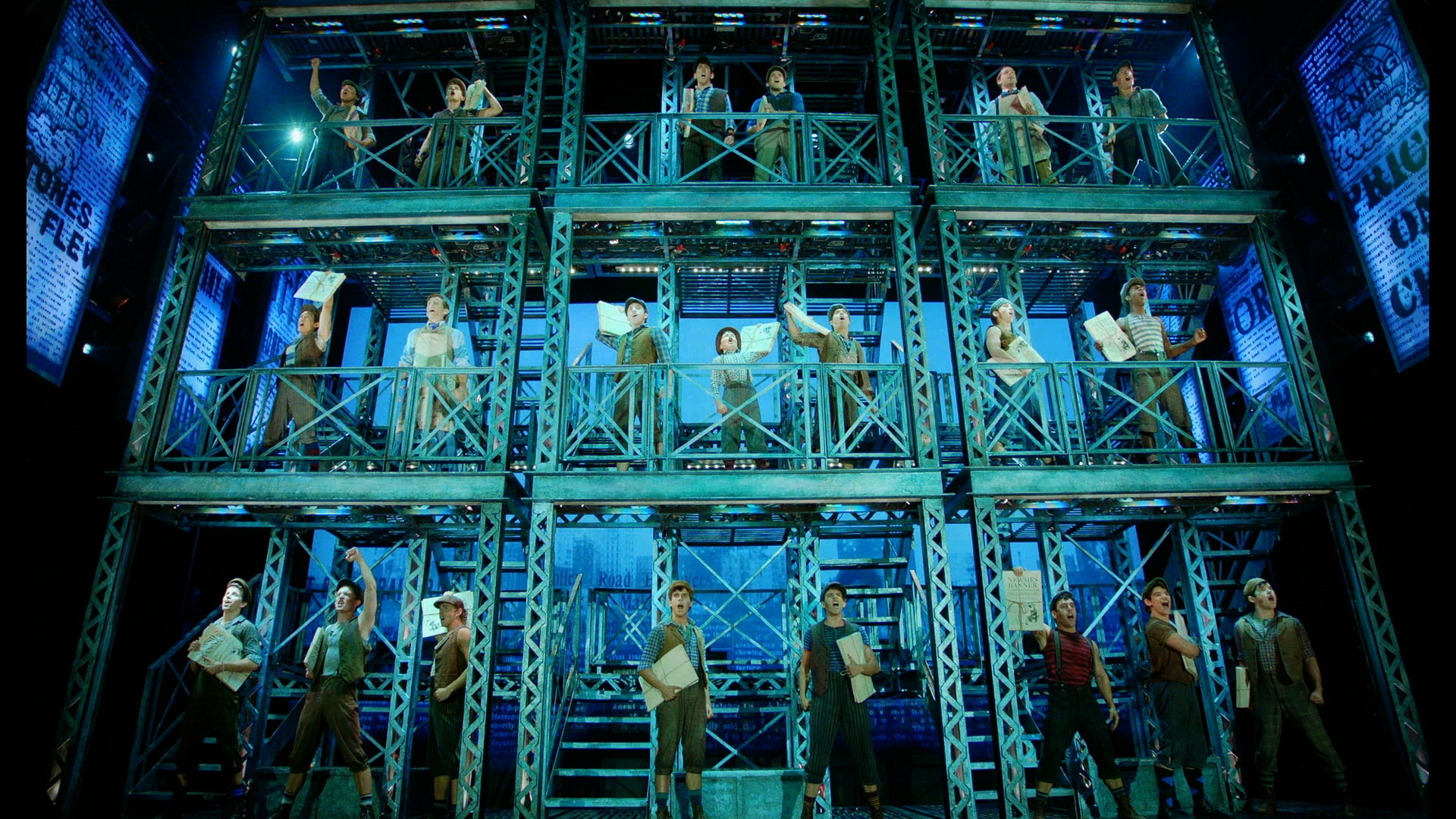 The Newsies cast performing on stage on a tiered structure