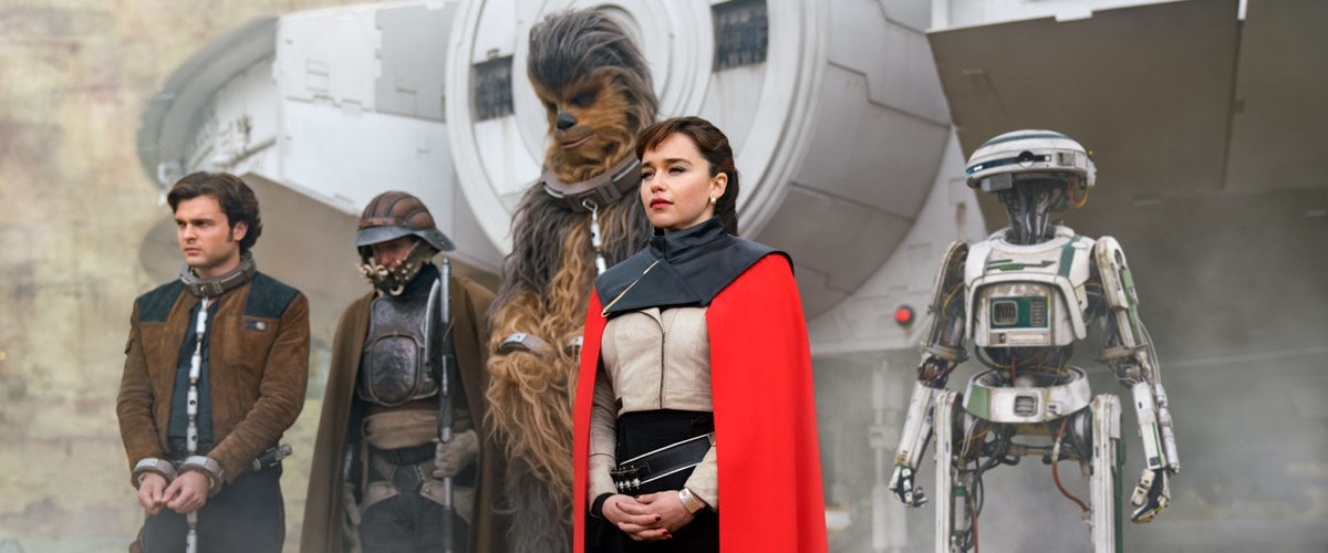 Qi'ra and Beckett's gang standing in front of the Millennium Falcon
