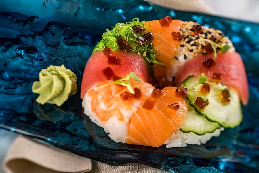 Image of sushi donut with a dollop of wasabi next to it