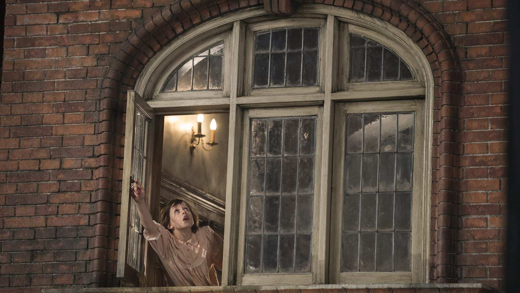"""Sophie (played by Ruby Barnhill) looking out a window in the movie """"The BFG"""""""