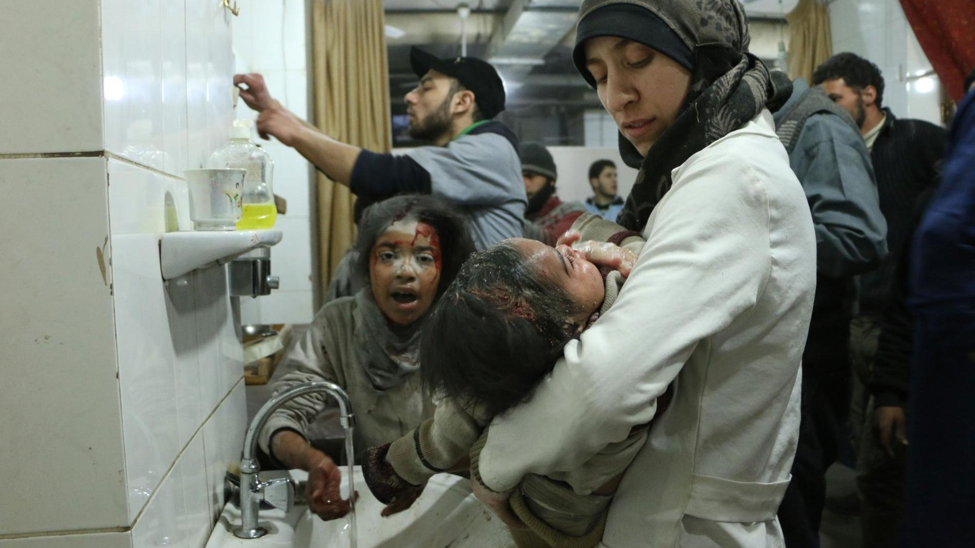 Al Ghouta, Syria - Dr. Amani (R) treats an injured baby amongst other medical staff and victims. (Photo by National Geographic)