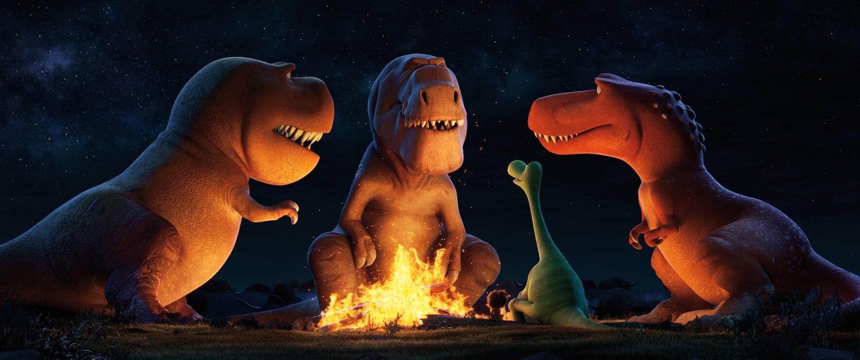 "Sam Elliott (Butch), Anna Paquin (Ramsey), A.J. Buckley (Nash), Raymond Ochoa (Arlo), and Jack Bright(Spot) sitting at a camp fire in ""The Good Dinosaur"""