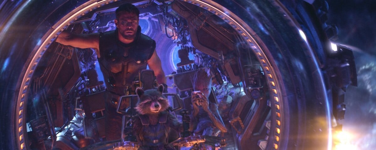 Thor, Rocket, and Groot sit in a space ship, in purple lighting in a scene from Avengers: Infinity War.