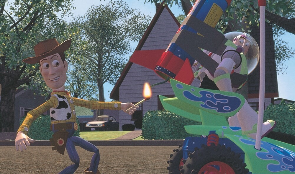 Woody holding a lit match to a firecracker taped to Buzz Lightyear's rocket