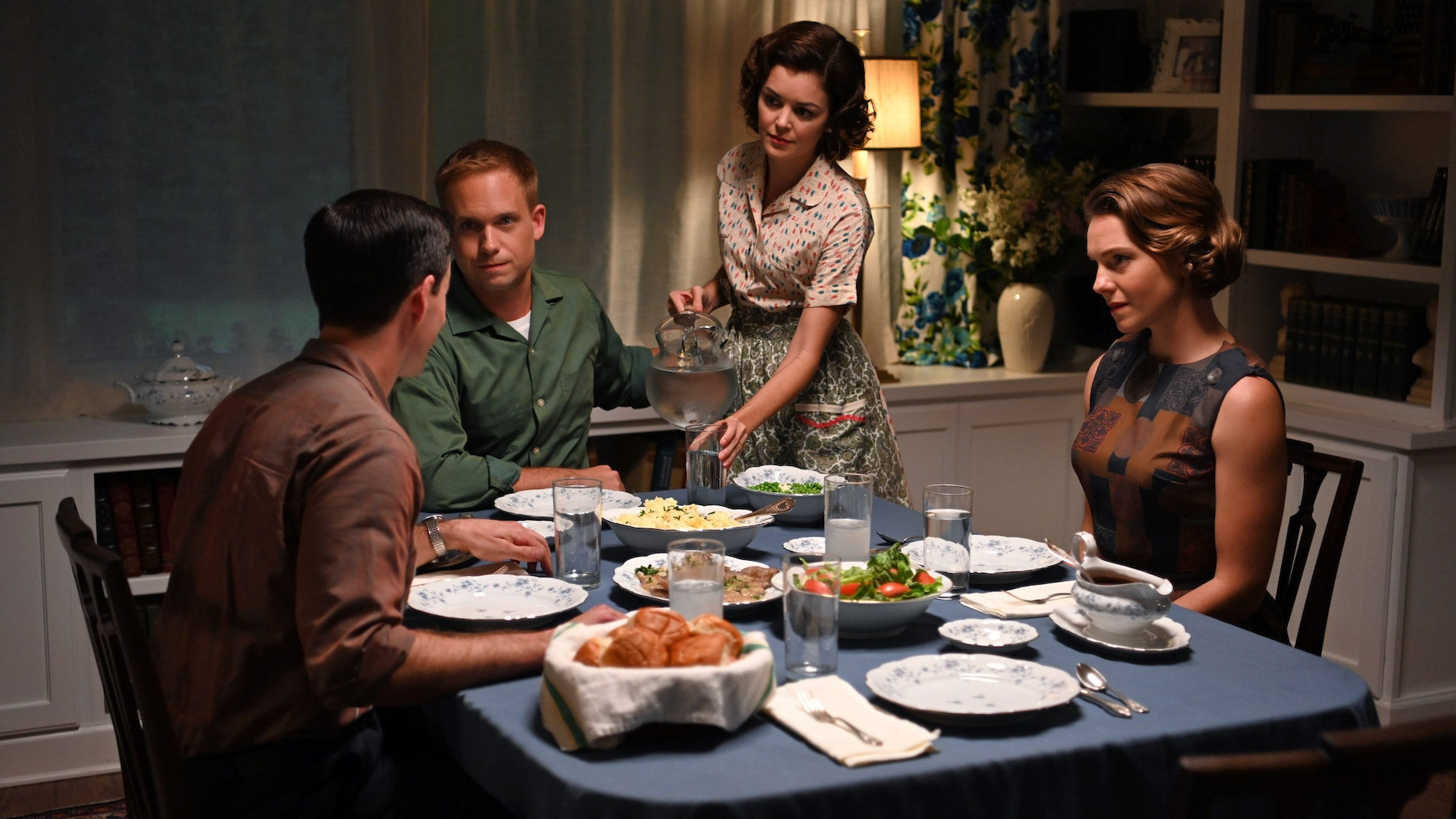 John Glenn played by Patrick J. Adams and Annie Glenn played by Nora Zehetner host Gordon Cooper played by Colin O'Donoghue and Trudy Cooper played by Eloise Mumford for dinner in National Geographic's THE RIGHT STUFF streaming on Disney+. (National Geogra