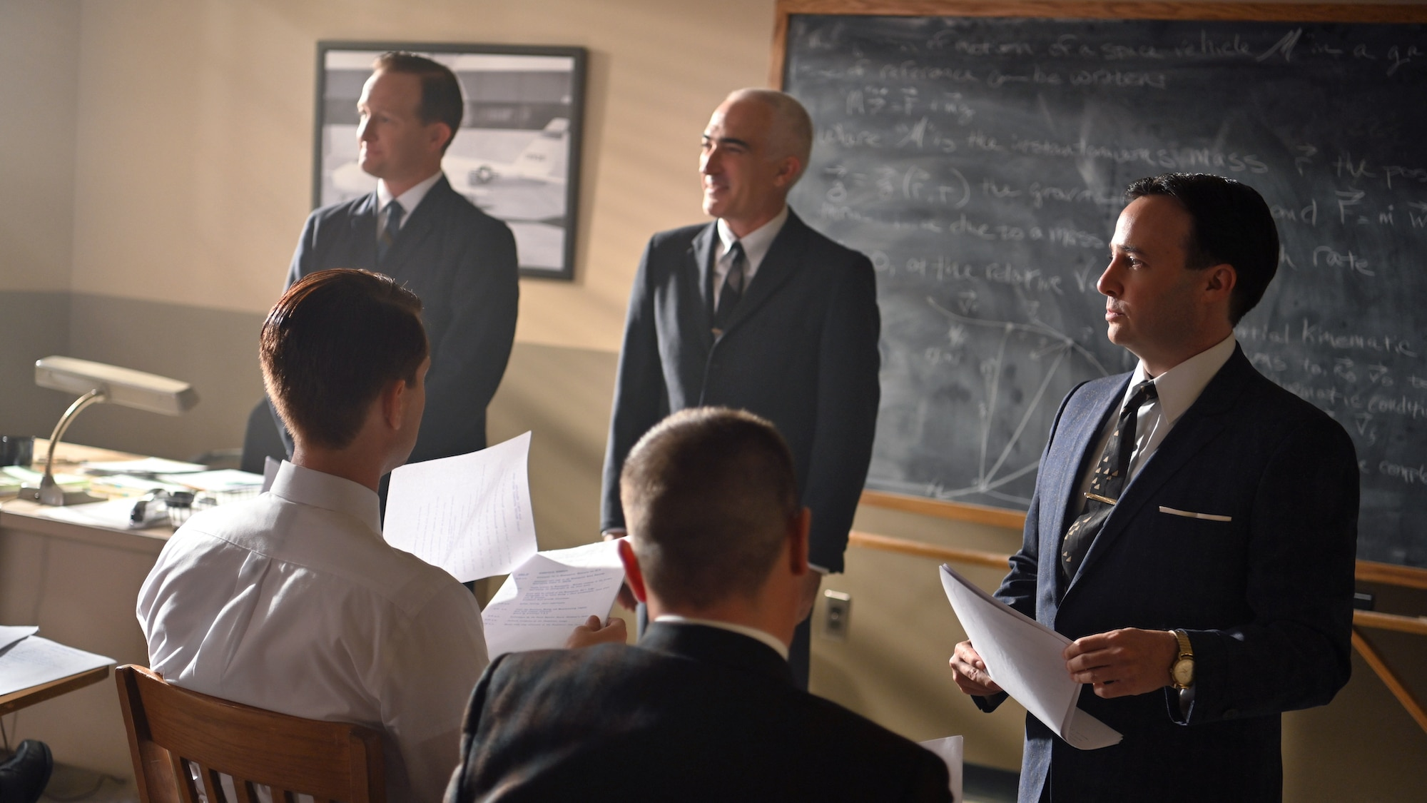 """Standing L to R: Chris Kraft played by Eric Ladin, Bob Gilruth played by Patrick Fischler and John """"Shorty"""" Powers played by Danny Strong speak to the Mercury astronauts about space program public relations."""