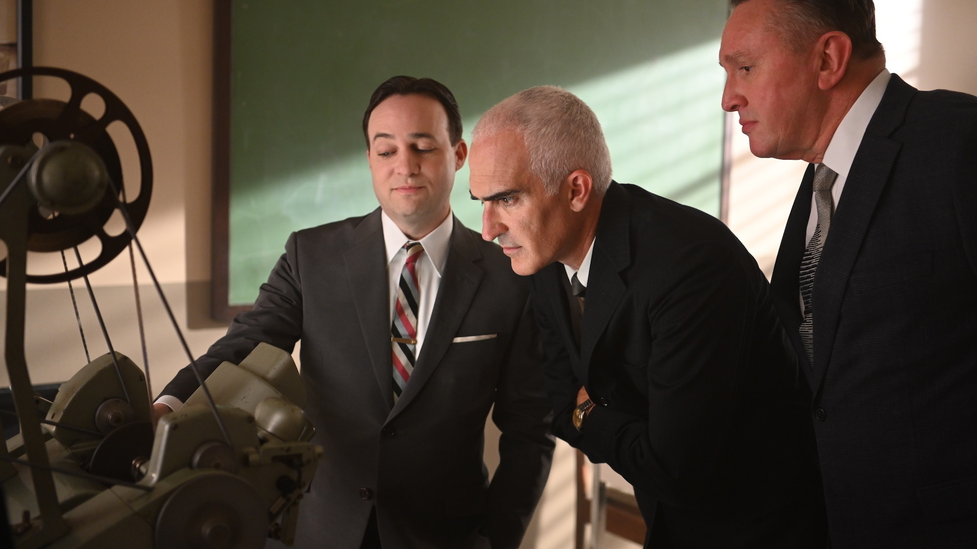 """L to R: John """"Shorty"""" Powers played by Danny Strong, Bob Gilruth played by Patrick Fischler and T. Keith Glennan Administrator of NASA played by Holland Hayes review press conference footage of the seven Mercury astronauts in National Geographic's THE RIG"""