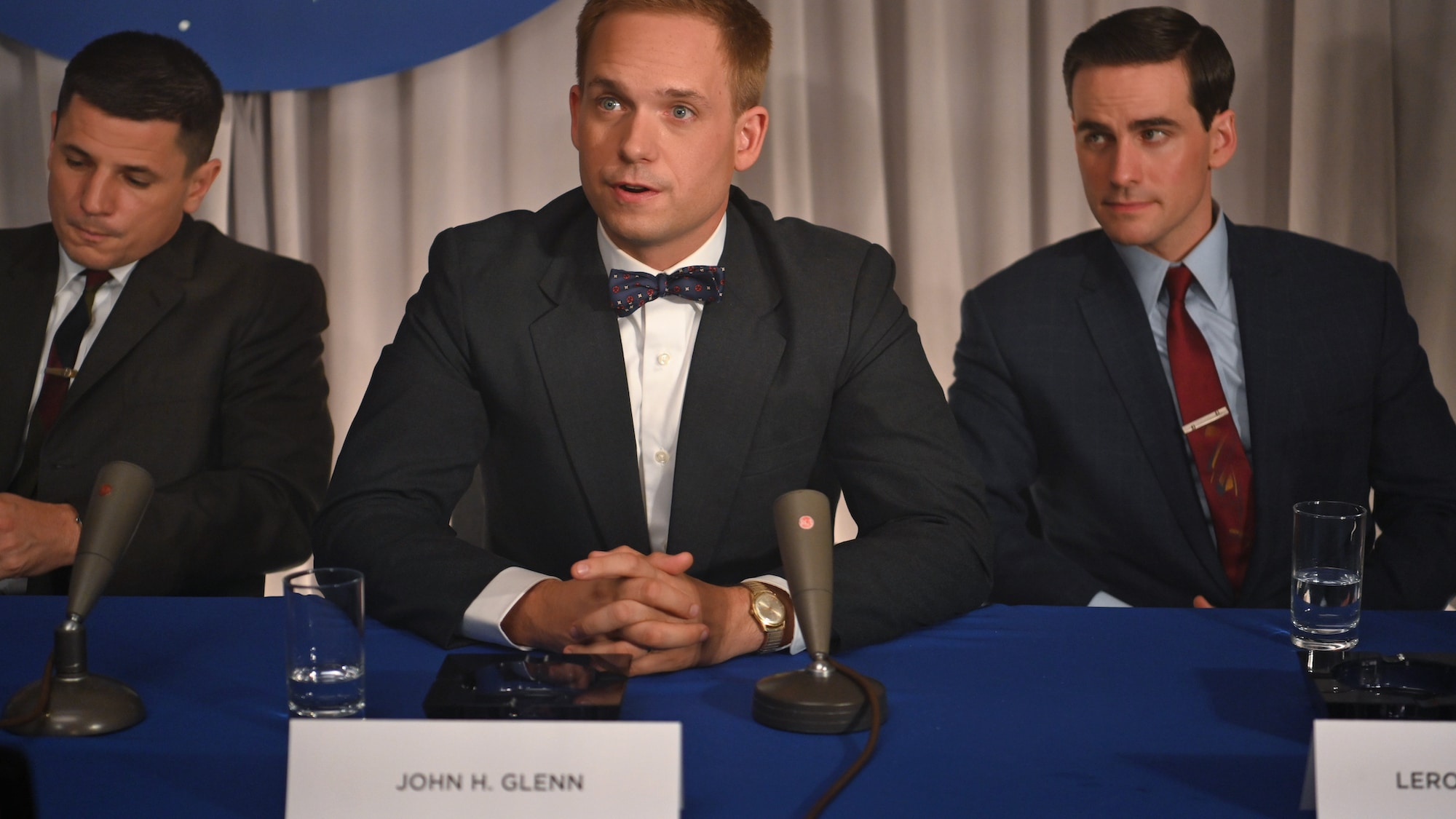 Mercury astronauts, John Glenn (center) played by Patrick J. Adams, Gus Grissom (L) played by Michael Trotter and Gordon Cooper (R) played by Colin O'Donoghue, during a press conference in National Geographic's THE RIGHT STUFF streaming on Disney+.