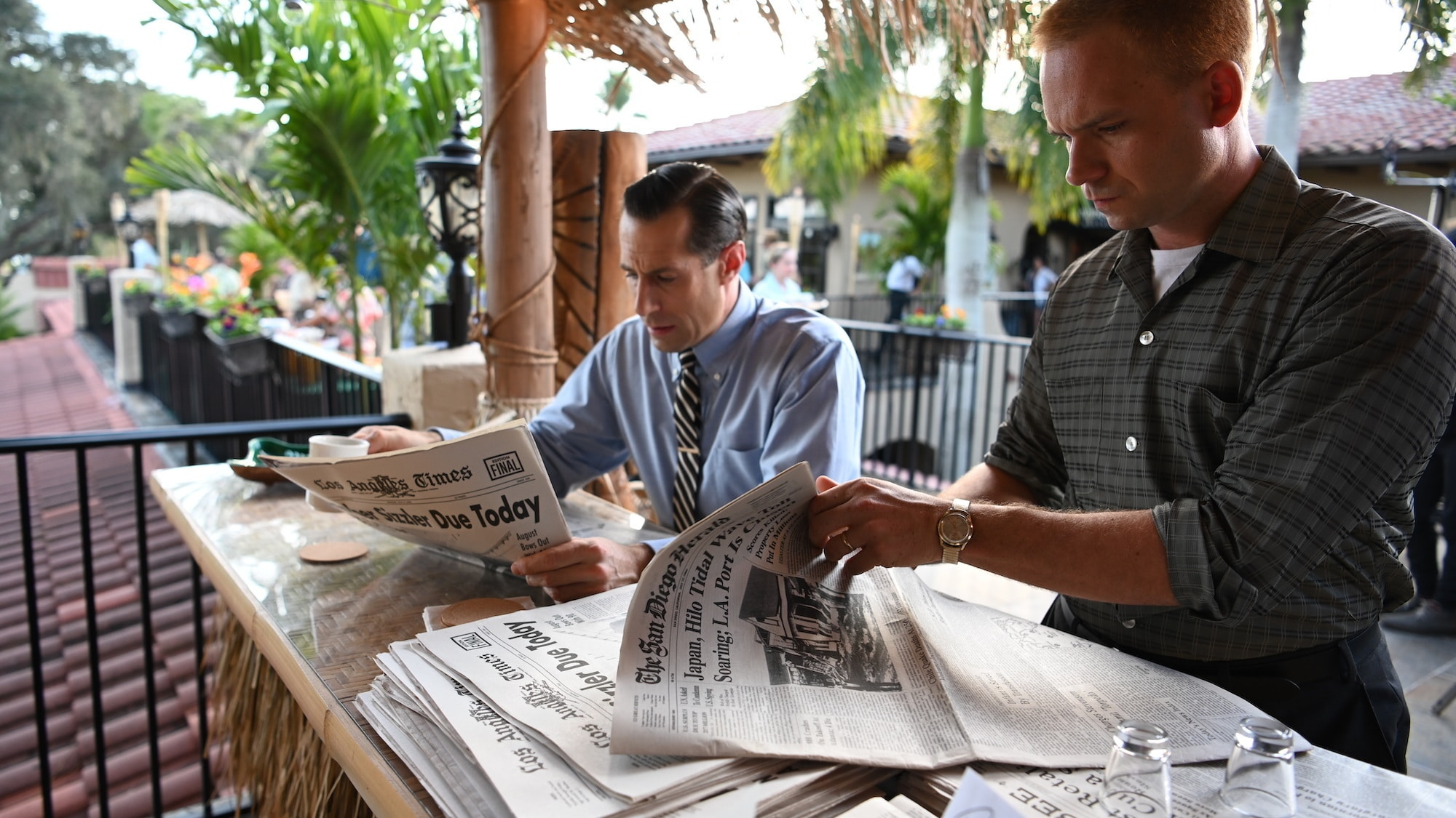 L to R: LIFE Magazine reporter Loudon Wainwright played by Josh Cooke reads the newspaper while John Glenn played by Patrick J. Adams examines it for a scandal involving a Mercury astronaut in National Geographic's THE RIGHT STUFF streaming on Disney+. (National Geographic/Gene Page)