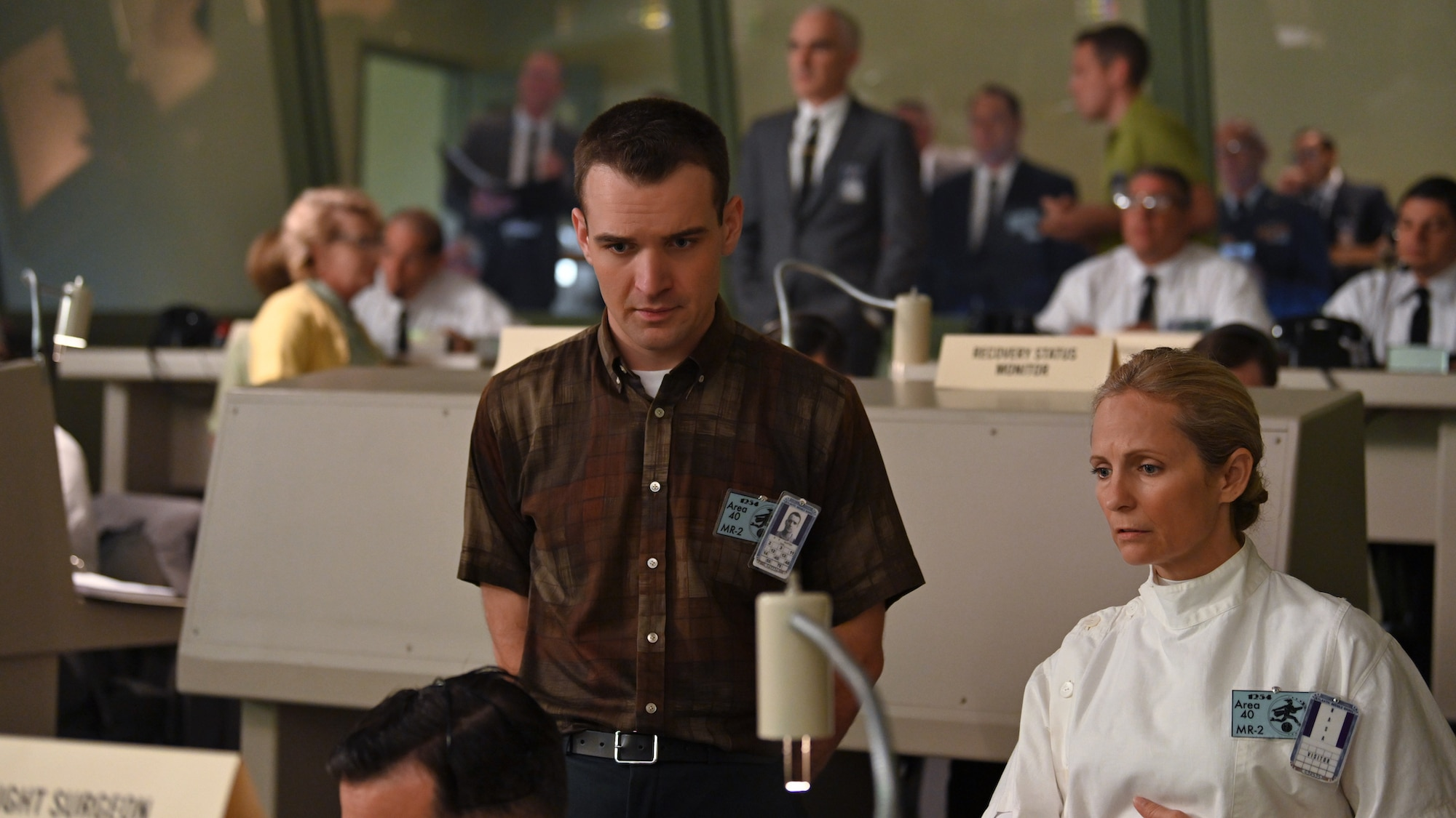 Micah Stock as Deke Slayton (front center) in Mercury Control Center during crucial rocket launch carrying a chimpanzee in National Geographic's THE RIGHT STUFF streaming on Disney+. (National Geographic/Gene Page)