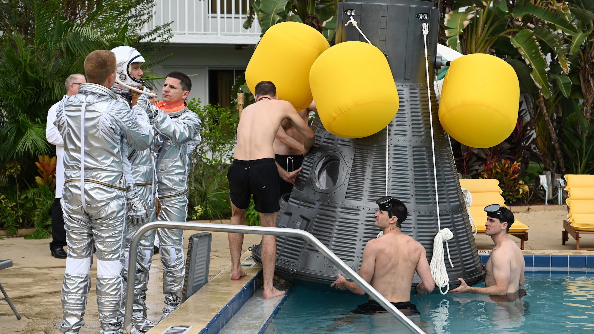 Mercury Seven astronauts during an emergency procedure demonstration in a swimming pool for Dr. Jerome Wiesner and other members of the President's Science Advisory Committee (not pictured) in National Geographic's THE RIGHT STUFF streaming on Disney+. (Credit: National Geographic/Gene Page)