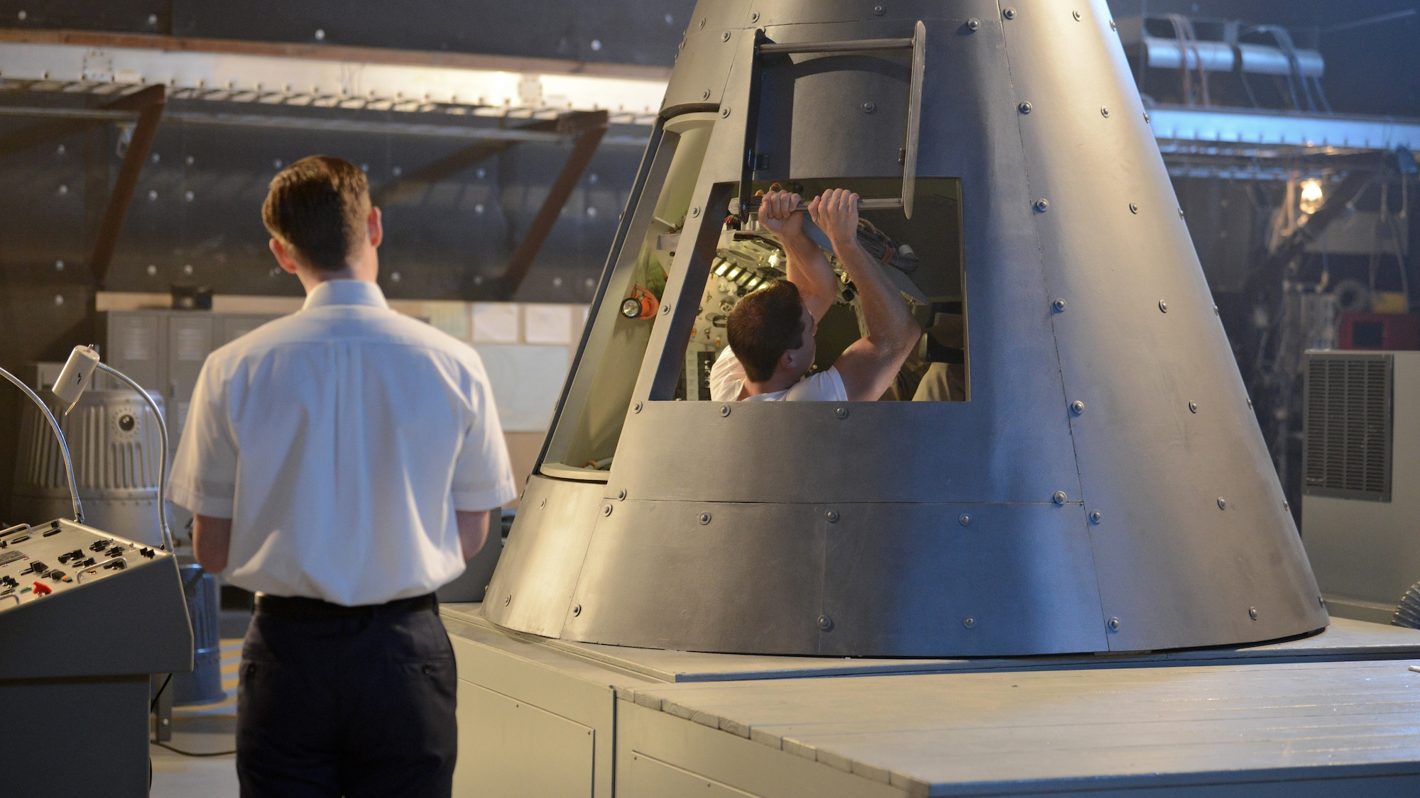 Glynn Lunney (L) played by Jackson Pace stands by while Alan Shepard played by Jake McDorman enters the trainer capsule during a practice session in National Geographic's THE RIGHT STUFF. (Credit: National Geographic/Gene Page)