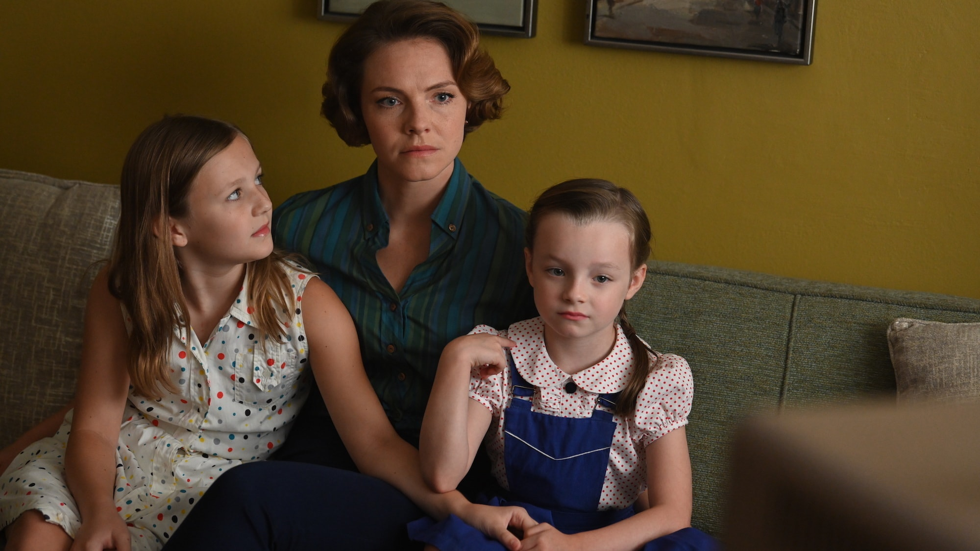 Trudy Cooper, played by Eloise Mumford, watches a press conference on TV with her daughters in National Geographic's THE RIGHT STUFF streaming on Disney+. (Credit: National Geographic/Gene Page)