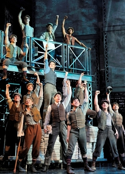 The cast of Newsies performing on stage, fists raised in protest