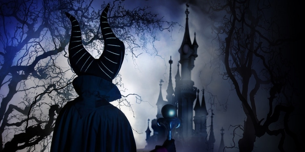 Maleficent facing away towards Sleeping Beauty's castle, surrounded by mist