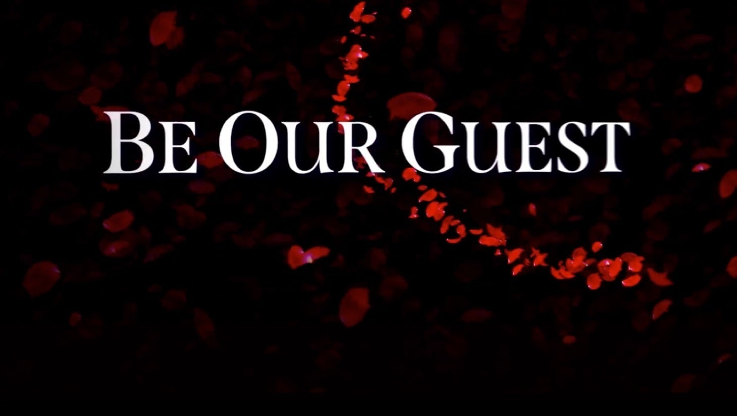 """""""Be Our Guest"""" written on a dark background with rose petals"""