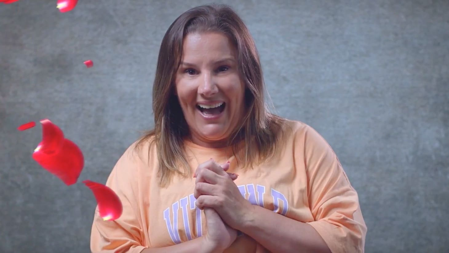 Actress Sam Bailey, clasping her hands together and smiling whilst looking at the camera