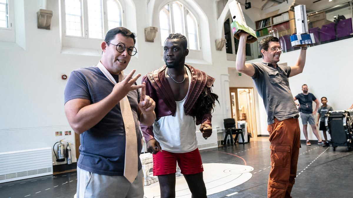 Nigel Richards as Cogsworth is counting on his fingers, Emmanuel Kojo as Beast is actively listening to him and Gavin Lee as Lumiere is standing cheerfully on the side.