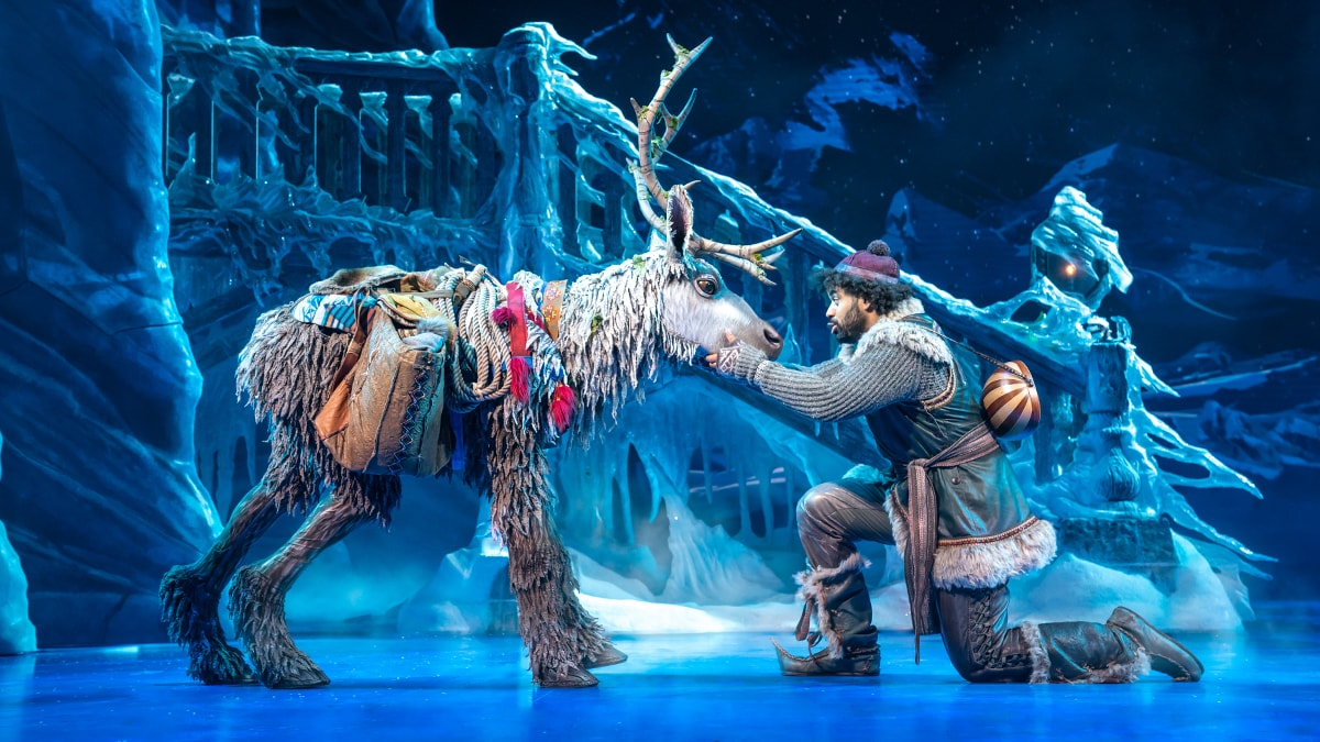 Kristoff holding Sven's face with his hands in front of an ice bridge.