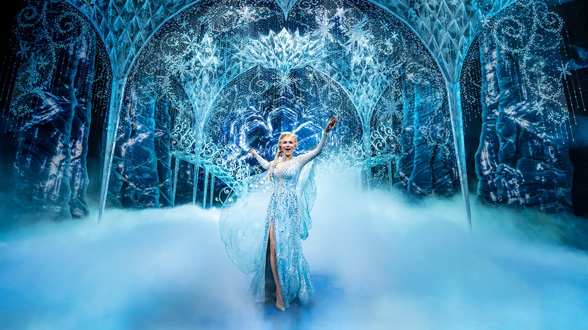 Elsa with her hands in the air surrounded by fog in the Ice Palace.