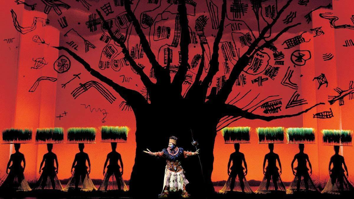 Rafiki in front of a silhouette of a tree in the stage show The Lion King