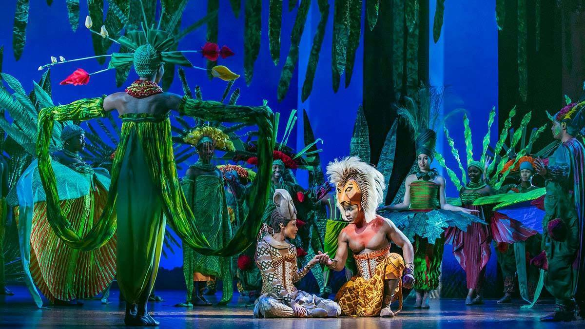Simba and Nala surrounded by actors posing as greenery in the stage show The Lion King
