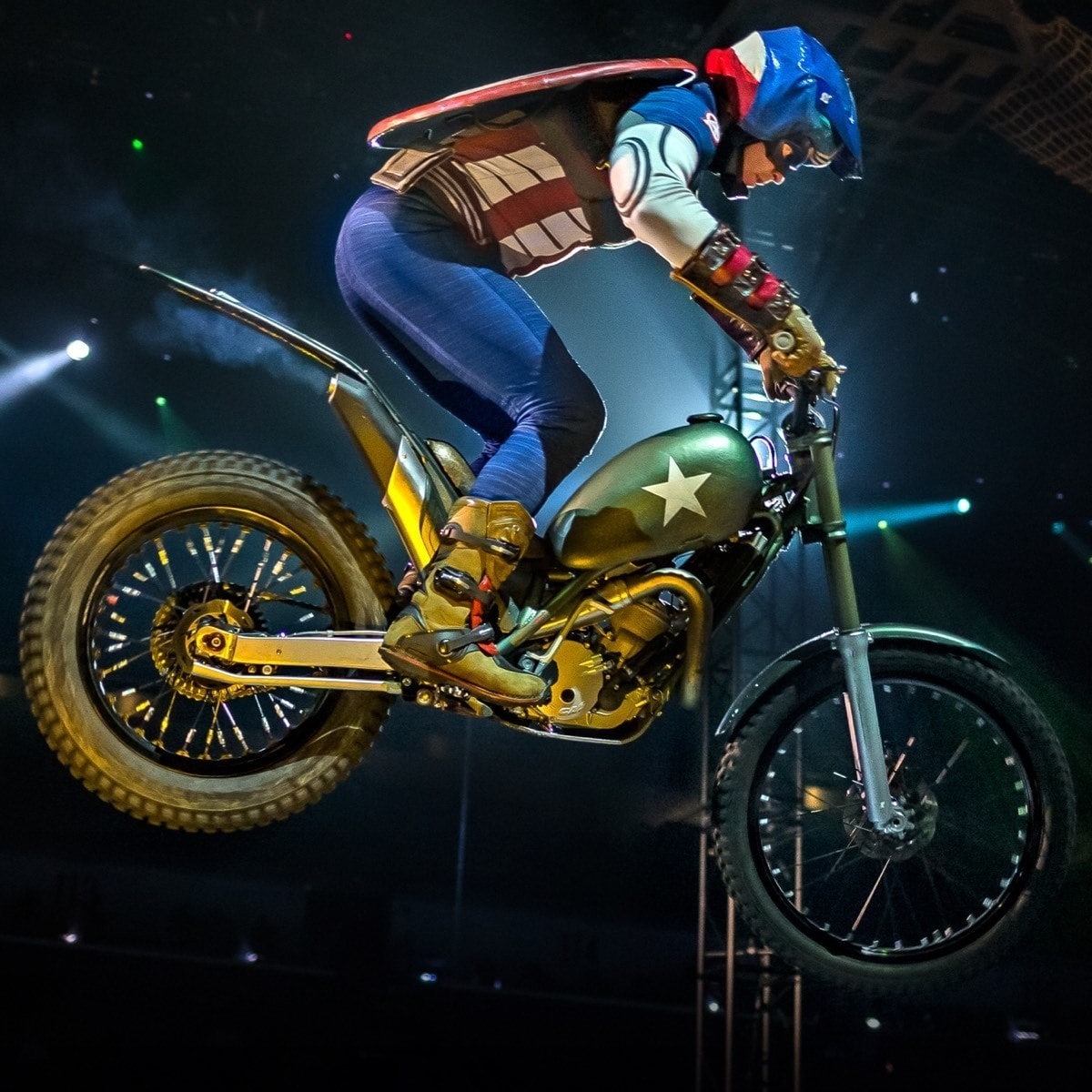 Captain America jumping a dirt bike with stage lights in the background