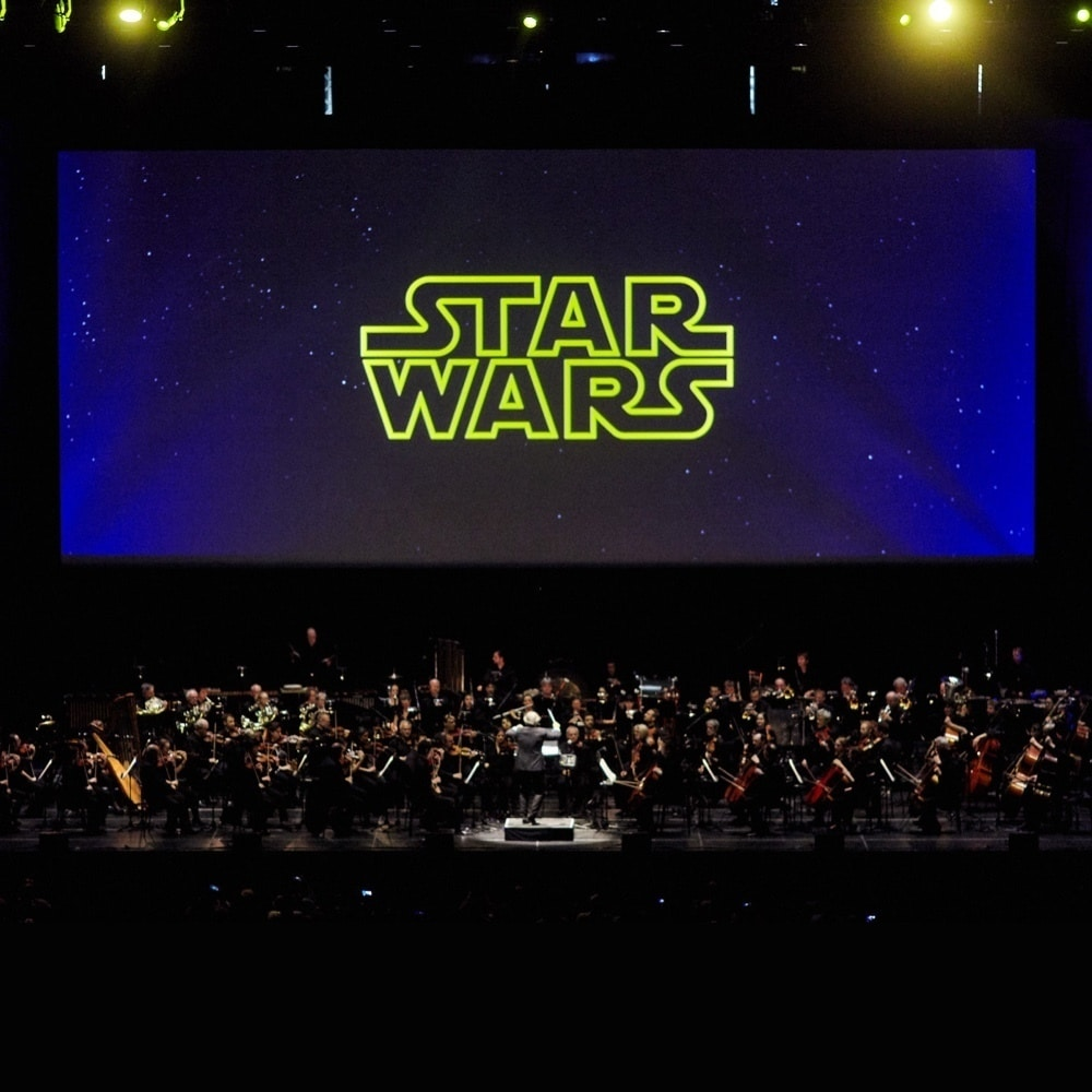 An orchestra on stage playing instruments whilst the Star Wars logo is featured on a large screen in the background