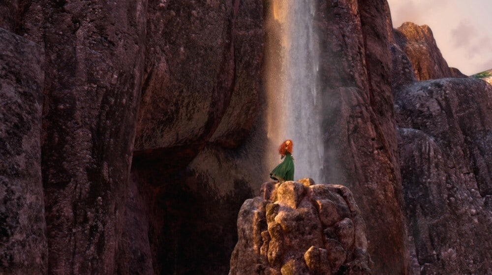 Merida on the top of a rocky cliff with a waterfall behind her