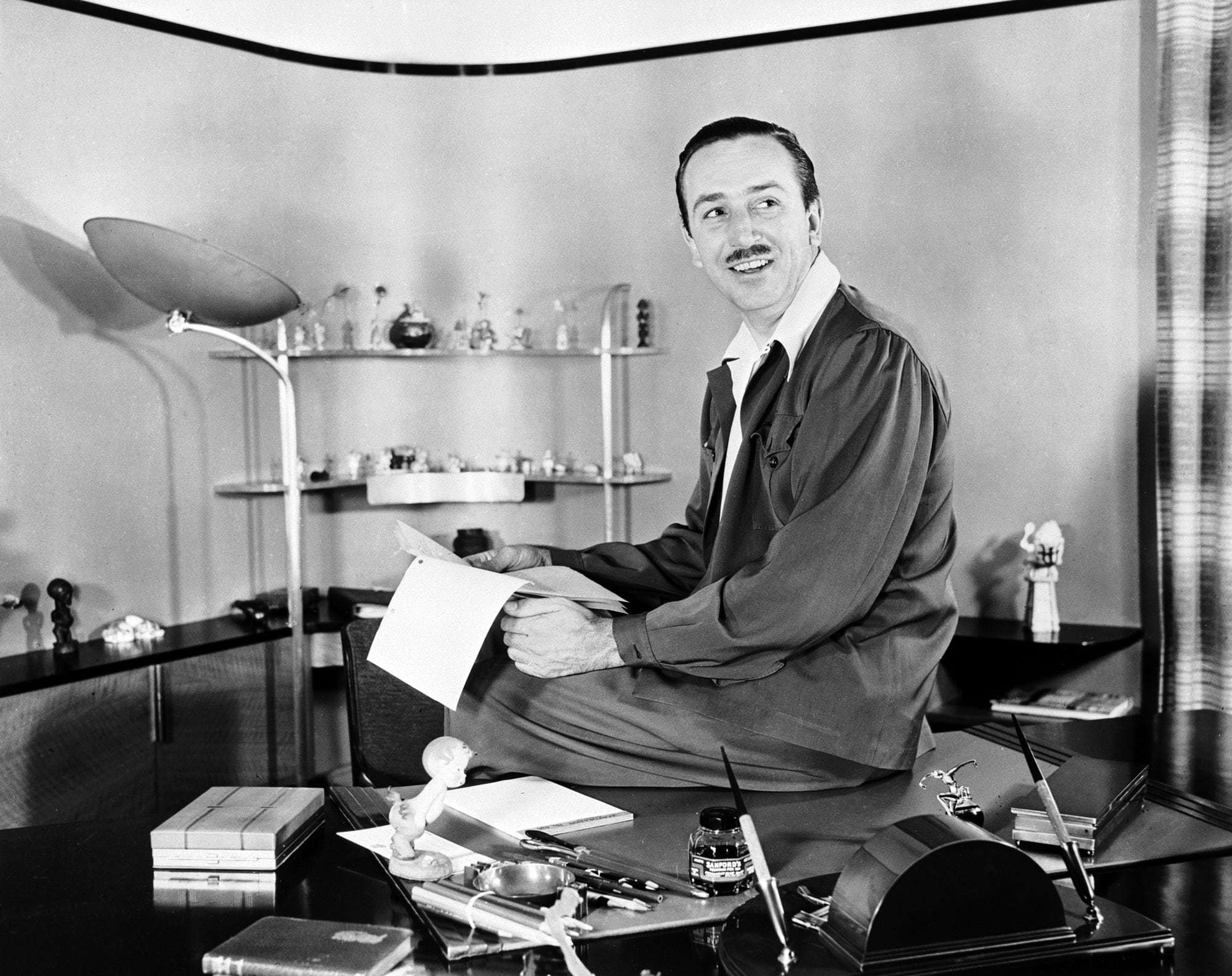 Walt Disney sitting at his desk