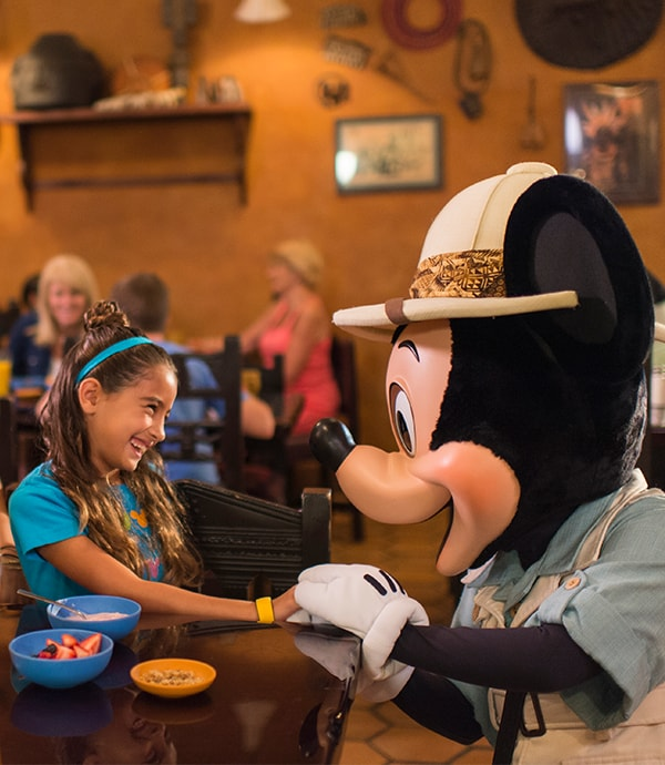 Mickey Mouse dressed in a safari suit holing a young girls hand at breakfast