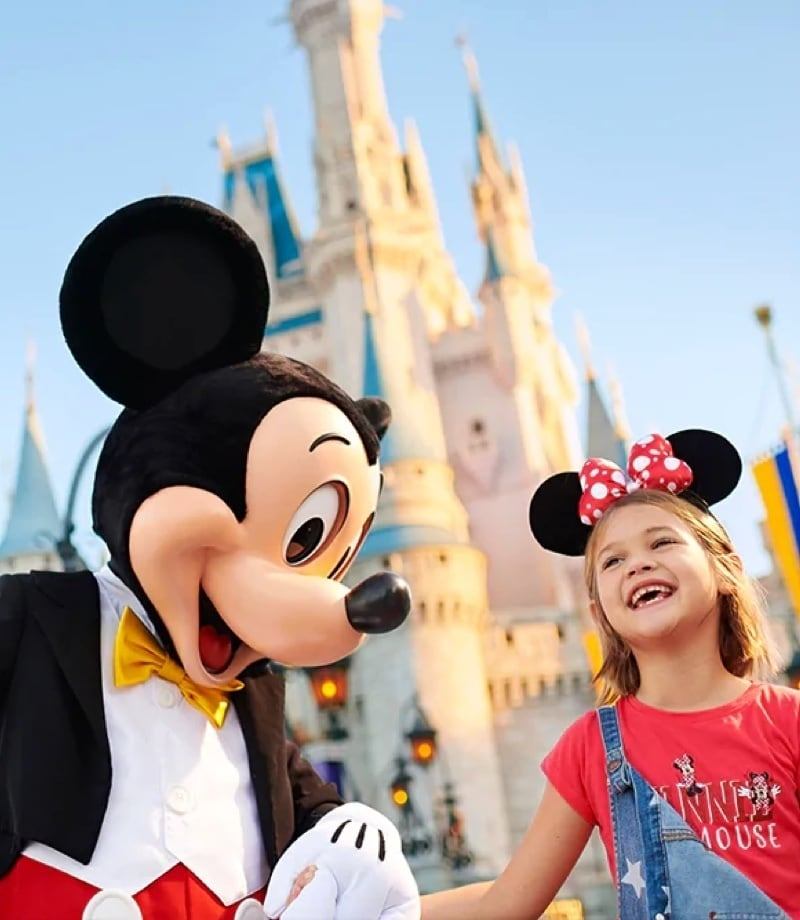 Mickey holding hands with a child at Walt Disney World
